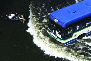 11月5日,在曼谷洪水蔓延的街道上,乘坐小船的居民与一辆公共汽车相遇。 新华社/路透
