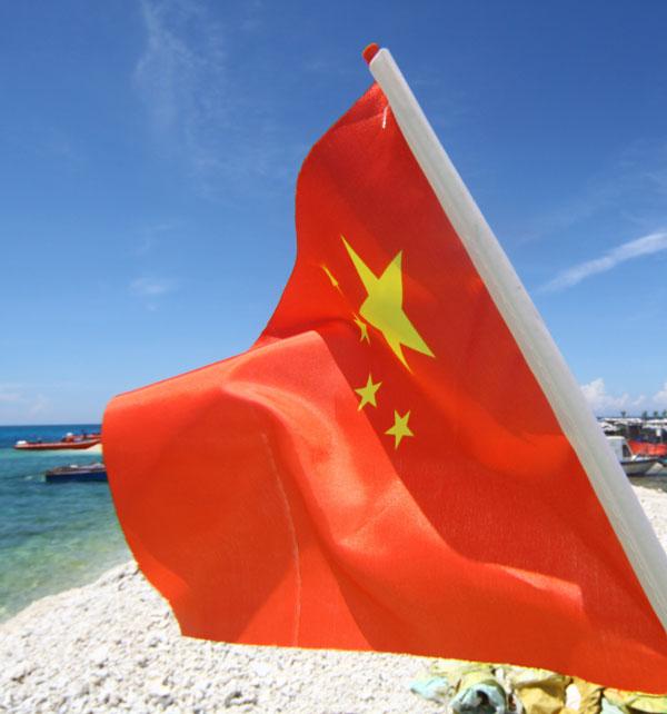鸭公岛上,游客带去的五星红旗迎风招展.图片