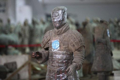 """2月23日,在陕西省秦始皇帝陵博物院兵马俑一号坑,一些修复中的兵马俑披上了""""纱衣"""",围着""""白色丝巾"""",萌翻参观的游客。图/CFP"""