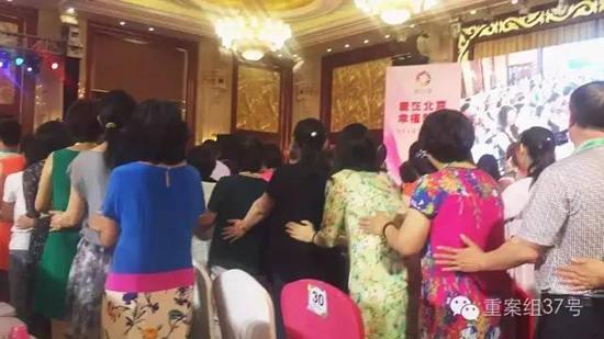 """六月初,北京盛典现场,主持人鼓励大家排起队,相互拍打身体,大喊""""财大气粗,腰缠万贯""""。"""