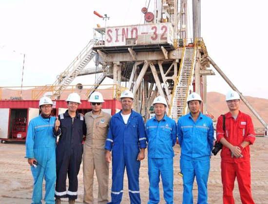 2015年8月14日,中石化中原油田员工与沙特阿美石油公司员工在沙特东部一油田钻井平台前合影。新华社记者王波摄