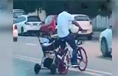男子骑车推婴儿车横穿马路